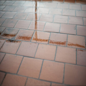 What caused A tile floor to be wet? When there was no rain.